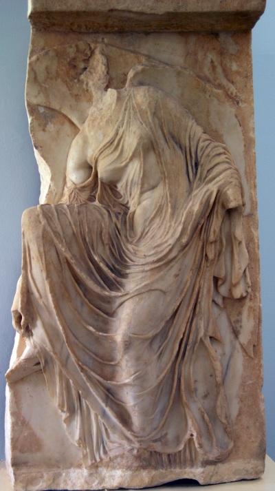 Nikè à la sandale. Une des plaques de la bande sculptée qui entourait le temple d'Athéna Nikè sur trois côtés : elle était située sur le côté Sud. Une Nikè est représentée penchée vers l'avant, peut-être pour dénouer sa sandale et marcher pieds nus vers l'autel qui devait être représenté devant elle, mais qui est perdu. Vers 420-410 av. J.-C.