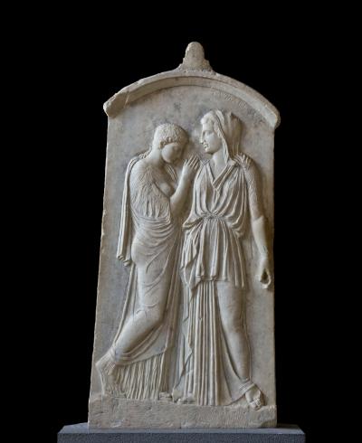 Pierre tombale de Krito et Timarista. Trouvé au cimetière de Camiros. Timarista, la mère défunte, et sa fille Krito sont représentées debout et s'embrassant. La forme de la stèle, et le fleuron sommital inhabituel, le rendu des personnages en bas-relief et l'intensité émotionnelle de la scène caractérisent un travail ionique, inspiré de Phidias. Marbre. 420-410 avant notre ère.